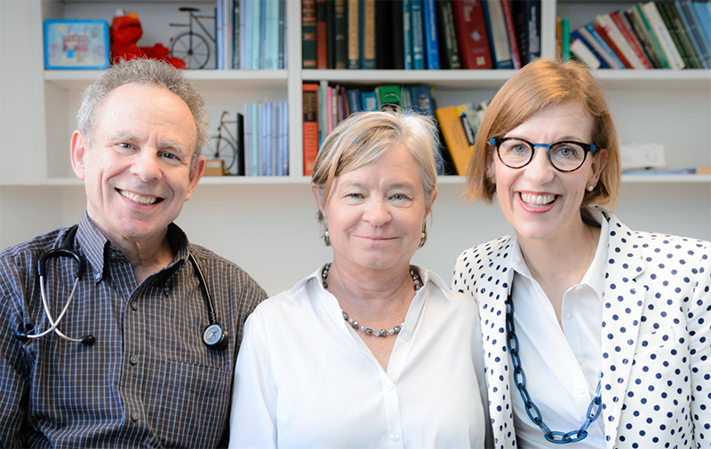 Dr. Bennett, Dr. Ahlstrom and Dr. de la Croix-Vaubois standing in the office in front of medical bookshelf