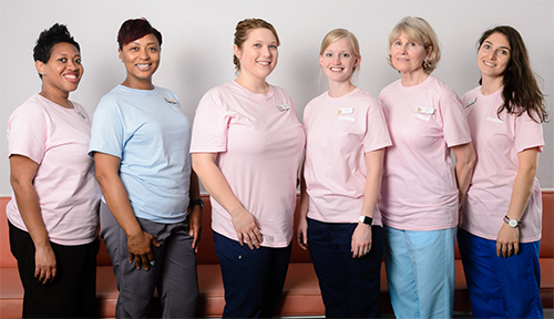 Staff of Chevy Chase Pediatrics, five women wearing blue and pink shirts